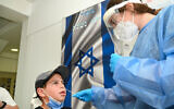 Un employé du Magen David Adom dépiste un enfant au coronavirus à Katsrin, sur le plateau du Golan, le 15 septembre 2021. (Crédit : Michael Giladi/Flash90)