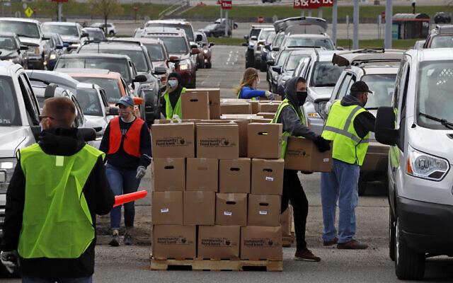 Dans une partie du parking de l'aéroport international de Pittsburgh laissée vacante par la pandémie de COVID-19, des bénévoles de la Greater Pittsburgh Community Food Bank chargent des boîtes de nourriture dans des voitures lors d'une distribution alimentaire en voiture, le 22 avril 2020. (Crédit : AP Photo/Gene J. Puskar)