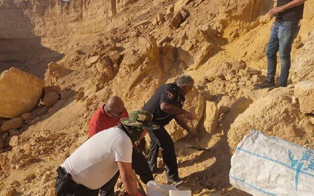 Des policiers transfèrent des restes humains trouvés dans le désert du Néguev pour qu'ils soient examinés par l'Institut de médecine légale, le 22 septembre 2021. (Crédit : Police israélienne)