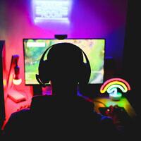 Illustration : On voit un jeune homme portant un casque et jouant à un jeu vidéo en ligne. (Crédit : DisobeyArt/iStock by Getty Images)