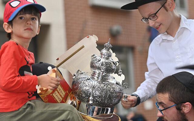Des enfants examinent un rouleau de la Torah alors qu'il est transporté dans la synagogue de la rue Vorosmarty à Budapest, en Hongrie, le 27 août 2021. (Crédit : Cnaan Liphshiz via JTA)
