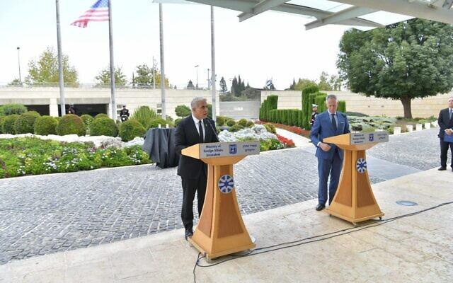 Le ministre des Affaires étrangères Yair Lapid, à gauche, et le Chargé d'Affaires de l'ambassade des États-Unis en Israël Michael Ratney lors d'une cérémonie à Jérusalem en commémoration du 20è anniversaire des attentats du 11 septembre, le 12 septembre 2021. (Crédit : Shlomi Amsalem/GPO)