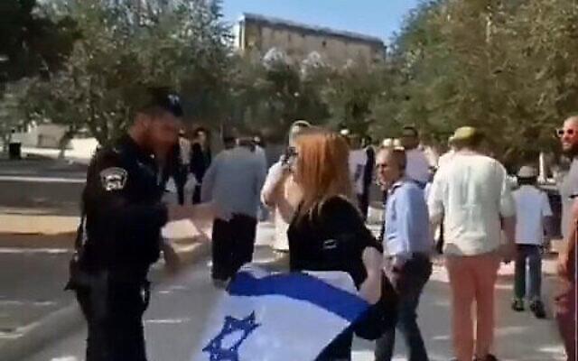 Un agent de police confisque un drapeau israélien à une femme sur le mont du Temple, le 27 septembre 2021. (Capture d'écran )