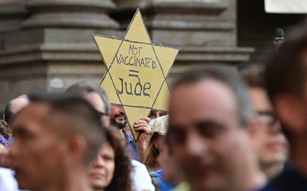 """Illustration : Un manifestant tient une étoile jaune sur laquelle on peut lire """"Pas de vaccin = Juif"""" alors que des manifestants prennent part à une manifestation à Milan, le 24 juillet 2021, contre l'introduction d'un """"laissez-passer vert"""" obligatoire pour les restaurants intérieurs et les lieux de divertissement, dans le but de limiter la propagation du coronavirus. (MIGUEL MEDINA / AFP)"""