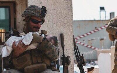 Matt Jaffe sourit à un bébé à l'aéroport de Kaboul en Afghanistan, vendredi 20 août 2021, dans une photo devenue virale. (Sergent Isaiah Campbell du Commandement central des États-Unis/US Marine Corps)
