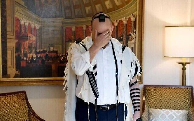 Le Premier ministre Naftali Bennett récite les prières du matin à son hôtel à Washington, le 25 août 2021. (Avi Ohayon/GPO)