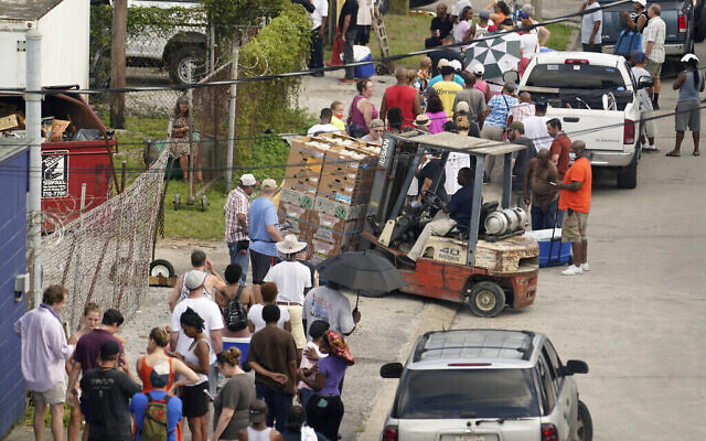 Après le passage de l'ouragan Ida, des personnes font la queue pour obtenir de la nourriture et de la glace dans un centre de distribution, le 1er septembre 2021, à La Nouvelle-Orléans, en Louisiane. (AP Photo/Eric Gay)