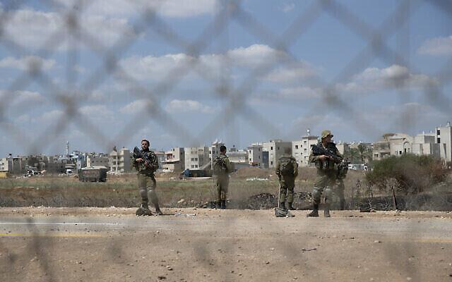 Des soldats israéliens montent la garde près d'une section endommagée de la clôture frontalière, près du village cisjordanien de Jalameh, le 6 septembre 2021. (AP/Nasser Nasser)