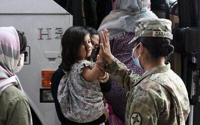 Une soldate américaine tape dans la main d'une fillette évacuée de Kaboul, en Afghanistan, avant de monter dans un bus après leur arrivée à l'aéroport international de Washington Dulles, à Chantilly, en Virginie, le 30 août 2021. (AP Photo/Jose Luis Magana, File)
