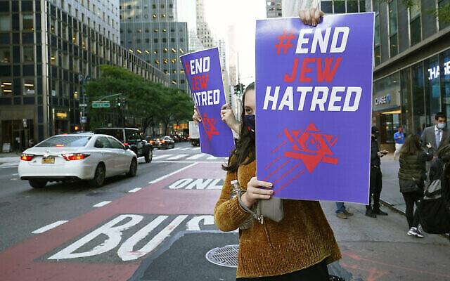 Une jeune femme tient une pancarte en direction de la circulation sur la 3e Avenue devant les bureaux du gouverneur de New York, Andrew Cuomo, jeudi 15 octobre 2020, à New York. (AP Photo/Kathy Willens)