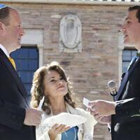 Sur cette photo fournie par Jocelyn Augustino, le rabbin Tirzah Firestone, au centre, officie une cérémonie de mariage juive traditionnelle à laquelle assistent la famille et les amis du gouverneur du Colorado Jared Polis, à gauche, et de son partenaire, Marlon Reis, à Boulder, Colorado, le 15 septembre 2021. (Jocelyn Augustino via AP)
