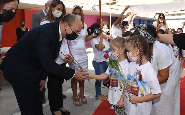 Le Premier ministre Naftali Bennett et la ministre de l'Éducation, le Dr Yifat Shasha-Biton, avec des enfants à l'école Eli Cohen Meuhad de Yeruham, lors de la rentrée scolaire, le 1er septembre 2021 (Haim Zach / GPO).
