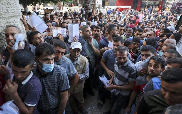 Des Palestiniens se rassemblent pour demander des permis de travail en Israël, au camp de réfugiés de Jabalia, dans le nord de la bande de Gaza, le 6 octobre 2021. (Crédit : Mahmud Hams / AFP)