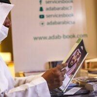 Un homme parcourt un livre portant sur sa couverture une image du prince héritier d'Arabie saoudite Mohammed ben Salmane alors qu'il visite un pavillon à la Foire internationale du livre de Ryad dans la capitale saoudienne le 9 octobre 2021 (Crédit : Fayez Nureldine / AFP)