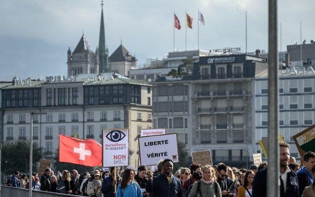 Des manifestants se rassemblent et tiennent des banderoles lors d'un rassemblement contre les mesures contre le coronavirus, le pass sanitaire Covid-19 et la vaccination à Genève, le 9 octobre 2021. (Crédit : Fabrice COFFRINI / AFP)