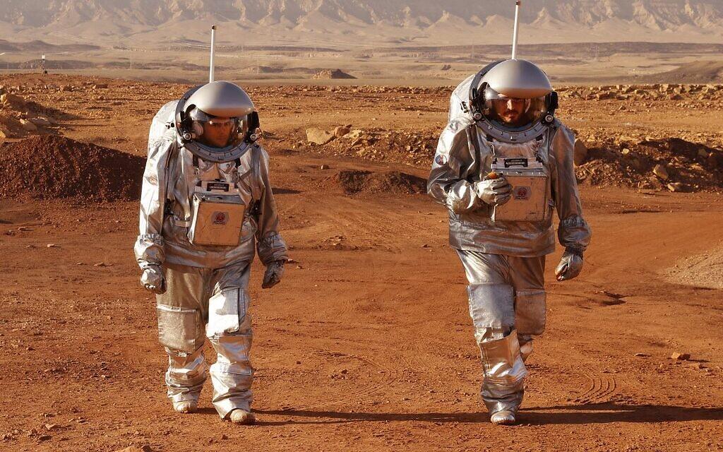 Un couple d'astronautes d'une équipe d'Europe et d'Israël marche en combinaison spatiale lors d'une mission d'entraînement pour la planète Mars sur un site qui simule une station hors site au cratère Ramon à Mitzpe Ramon, dans le sud du désert du Néguev en Israël, le 10 octobre 2021. (Crédit : JACK GUEZ / AFP)