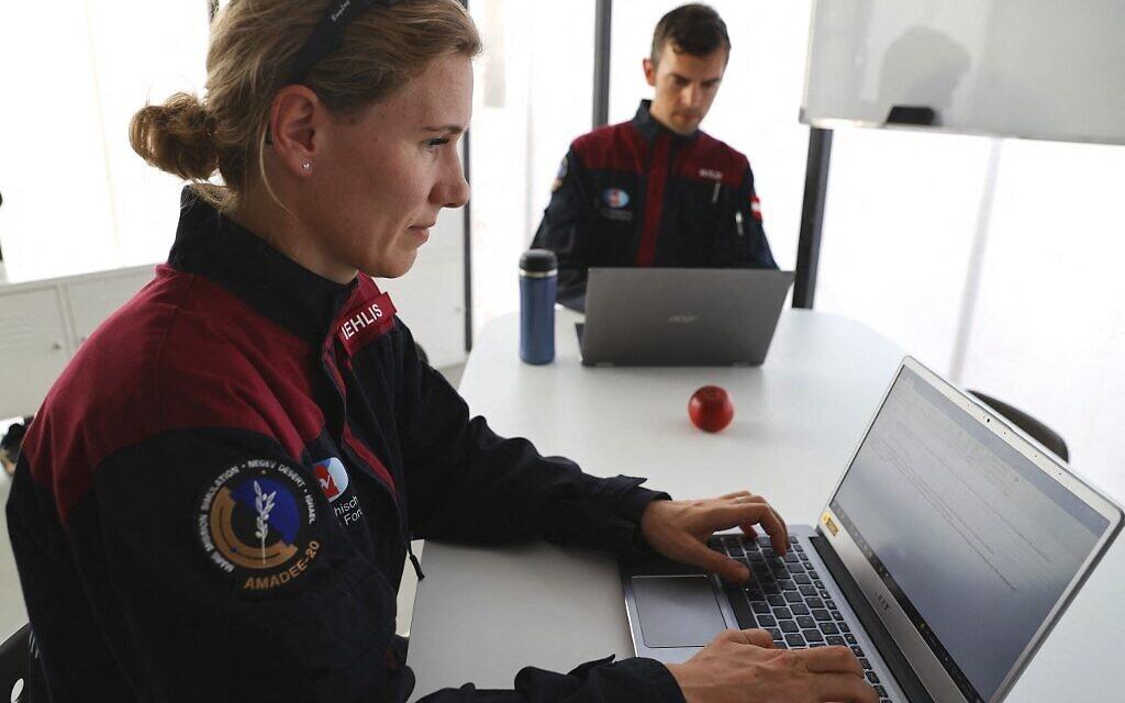 (De gauche à droite) L'astronaute allemande Anika Mehlis et son collègue autrichien Robert Wild utilisent des ordinateurs portables avant une mission d'entraînement pour la planète Mars sur un site qui simule une station hors site au cratère Ramon à Mitzpe Ramon, dans le sud du désert du Néguev en Israël, le 10 octobre 2021. (Crédit :  Jack Guez/AFP)