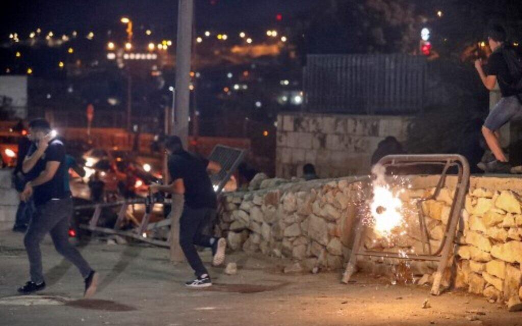 Des manifestants palestiniens alors qu'une grenade assourdissante explose lors d'une manifestation dans la Vieille Ville de Jérusalem, le 10 octobre 2021. (Crédit : AHMAD GHARABLI / AFP)