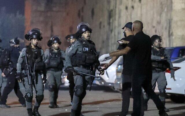 Des agents de la police des frontières affrontent des Palestiniens près de la porte du Lion, dans la Vieille Ville de Jérusalem, le 10 octobre 2021. (Crédit : AHMAD GHARABLI / AFP)