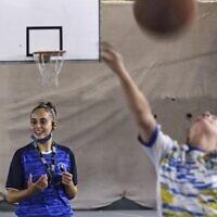 L'arbitre palestinienne Amira Ismail entraîne de jeunes basketteurs à l'Académie des champions dans la ville de Gaza, le 4 octobre 2021 (Crédit ; MOHAMMED ABED / AFP).