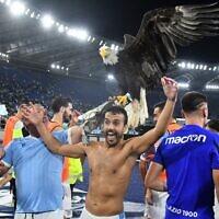 Illustration : Pedro Rodriguez Ledesma, attaquant espagnol de la Lazio, avec la mascotte de la Lazio, l'aigle Olimpia, après le match de la Lazio contre l'AS Roma au stade olympique de Rome, le 26 septembre 2021. (Crédit : Vincenzo PINTO / AFP)
