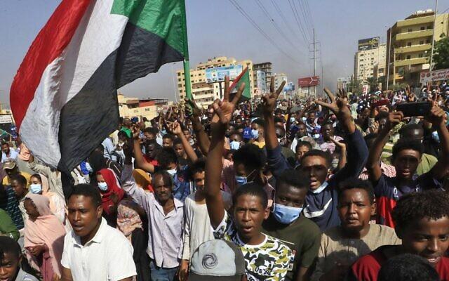 Des manifestants soudanais brandissent des drapeaux alors qu'ils se rassemblent sur la 60e rue à Khartoum, pour dénoncer les détentions nocturnes par l'armée de membres du gouvernement, le 25 octobre 2021. (Crédit : AFP)