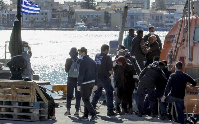 Des migrants débarquent d'un navire des garde-côtes après une opération sur l'île grecque de Chios, le 26 octobre 2021. (Crédit : Dimitris Vouchouris / Eurokinissi / AFP)