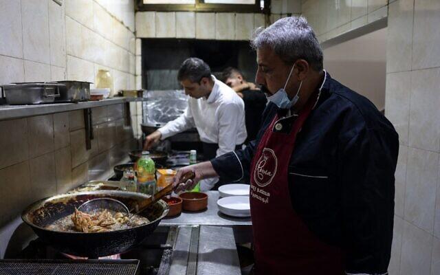 Moïn (à droite) et Mustapha Abou Hassira dans la cuisine du restaurant de poisson Roma appartenant à la famille Abou Hassira à Gaza, le 23 octobre 2021. (Crédit : MOHAMMED ABED / AFP)