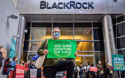 Un manifestant s'agenouille devant le siège de BlackRock à Manhattan, pour demander au PDG de la société d'investissement, Larry Fink, de ne pas financer l'industrie des combustibles fossiles, le 18 octobre 2021. (Crédit : Erik McGregor)