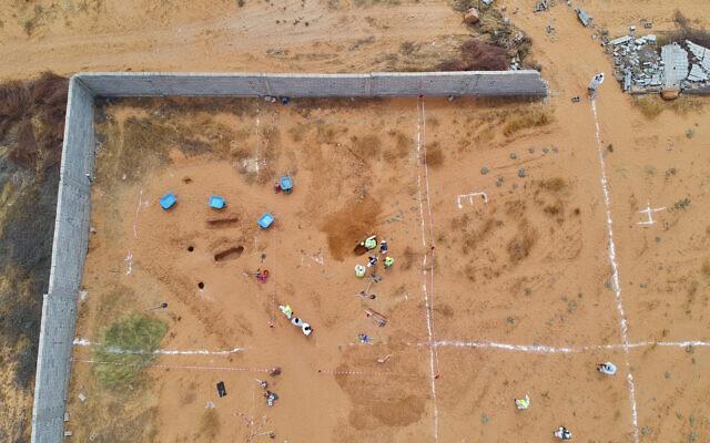 Des employés du ministère libyen de la justice creusent sur le site d'un charnier présumé dans la ville de Tarhouna, en Libye, le mardi 23 juin 2020. (Crédit :  AP/Hazem Ahmed)
