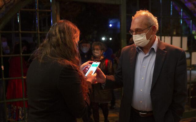Un homme montre son Passeport vert à son arrivée au théâtre Khan de Jérusalem, le 23 février 2021. (Crédit : AP Photo/Maya Alleruzzo, File)