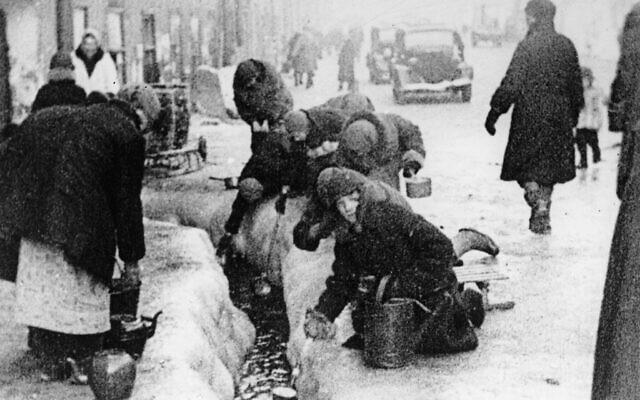 Des citoyens de Leningrad en train d'extraire de l'eau d'une canalisation brisée, pendant le siège de 900 jours de la ville russe par les envahisseurs allemands pendant l'hiver 1942. (Crédit : AP Photo, Archives)