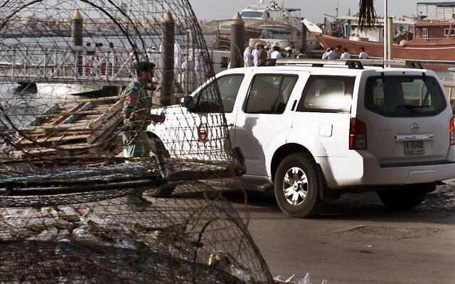 Photo d'illustration : La police émiratie et d'autres officiels inspectent un bateau dans un port de pêche du district de Jumeirah, à Dubaï, aux Emirats arabes unis, le 16 juillet 2012. (Crédit :   AP Photo/Almoutasim Almaskery)