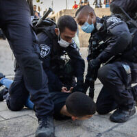 La police arrête un jeune Palestinien devant la porte de Damas, près de la vieille ville de Jérusalem, le 20 octobre 2021. (Crédit : Yonatan Sindel/Flash90)