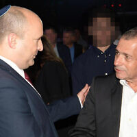 Le Premier ministre Naftali Bennett (à gauche) salue le chef sortant du Shin Bet, Nadav Argaman, lors d'un événement organisé en l'honneur du chef de la sécurité, le 14 octobre 2021 (Crédit : Amos Ben Gershom/GPO).