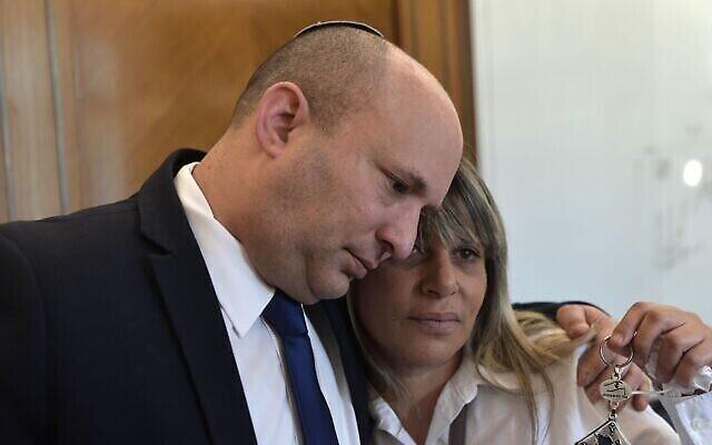 Le Premier ministre Naftali Bennett, à gauche, serre dans ses bras Nitza Shmueli, dont le fils Barel, garde-frontière, a été abattu par un tireur palestinien à la frontière de Gaza en août, au bureau du Premier ministre à Jérusalem, le 27 octobre 2021. (Crédit : Kobi Gideon/PMO)