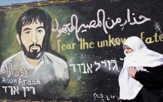 Une Palestinienne passe devant une peinture murale réalisée par un artiste du Hamas représentant le soldat israélien capturé Ron Arad, dans le camp de réfugiés de Jabalia, dans la bande de Gaza, le 28 janvier 2010. (Crédit : Abed Rahim Khatib/Flash90)