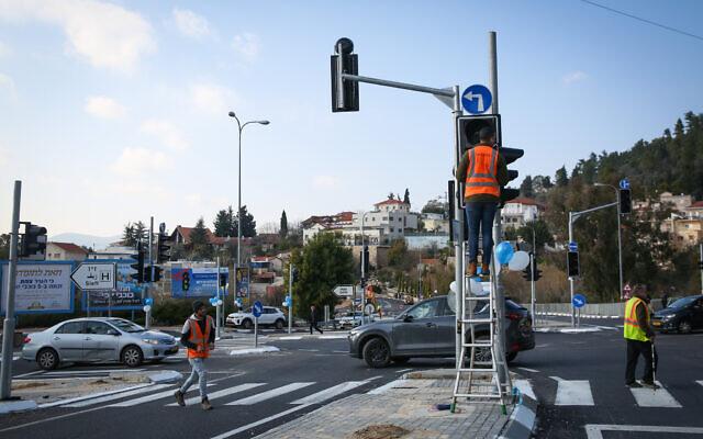 Illustration : des ouvriers actionnent un feu de circulation dans la ville de Tzfat, au nord d'Israël, le 14 janvier 2020. (Crédit : David Cohen/Flash90)