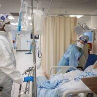 Des employés de l'unité de prise en charge du coronavirus, portant leurs équipements de protection, à l'hôpital Shaare Zedek de Jérusalem, le 23 septembre 2021. (Crédit : Yonatan Sindel/Flash90)