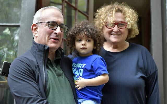 Le lauréat du prix Nobel d'économie Joshua Angrist, à gauche, s'adresse à un journaliste en compagnie de sa petite-fille Bella et de sa femme Mira Angrist, depuis son domicile, lundi 11 octobre 2021, à Brookline, dans le Massachusetts. (Crédit : Josh Reynolds/AP)