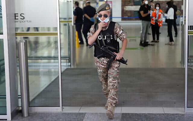 Illustration : une policière ajuste son masque alors qu'elle monte la garde à l'aéroport principal de Chypre à Larnaca, le mardi 9 juin 2020. (Crédit : AP Photo/Petros Karadjias)