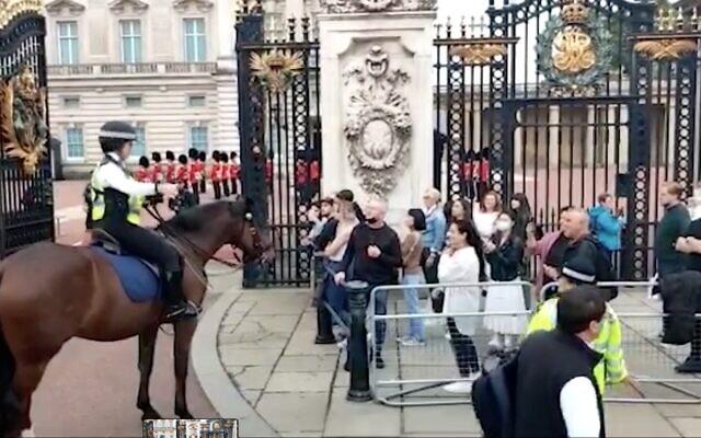 Capture d'écran de la vidéo d'un agent de la police métropolitainede Londres utilisant le langage des signes pour communiquer avec des touristes israéliens sourds devant le palais de Buckingham, le 3 octobre 2021. (Facebook)