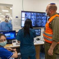 Le personnel de l'hôpital Shaare Zedek et un soldat de Tsahal réunis autour d'écrans d'ordinateur le 14 octobre 2021. (Crédit : Olivier Fitoussi/Flash90)