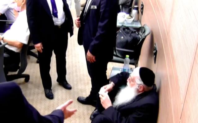 Le député de Yahadout HaTorah Meir Porush, assis par terre, récite des Psaumes pendant une réunion de la Knesset en protestation contre le député travailliste Gilad Kariv, le 7 octobre 2021. (Capture d'écran/Twitter)