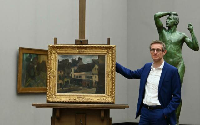 Ralph Gleis, historien de l'art et directeur de galerie allemand, à côté d'un tableau de Pissarro spolié par les nazis, le 18 octobre 2021. (Crédit : CHRISTOF STACHE / AFP)