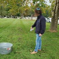 Le Dr Jonathan Weinkle de la Nouvelle Communauté Chevra Kadisha de Pittsburgh verse de l'eau dans le cadre de l'accomplissement du rituel de tahara ruchanit, ou purification spirituelle, le 3 octobre. (Crédit : Adam Reinherz/ Pittsburgh Jewish Chronicle via JTA)