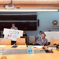 Les employés du ministère des Affaires étrangères perturbent une rencontre de la commission des promotions alors qu'un membre de la commission attend qu'ils quittent la salle, le 19 octobre 2021. (Crédit : Lazar Berman/Times of Israel)