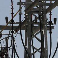 Image illustrative d'un ouvrier d'Israel Electric Corporation hissé par une grue sur un poteau électrique pour effectuer des travaux de maintenance, à l'extérieur de Jérusalem, le 10 juin 2013. (Crédit : Flash 90)