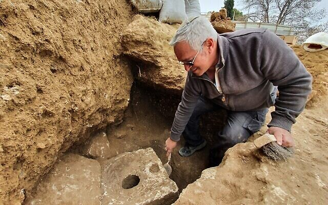 Yaakov Billig, archéologue de l'Autorité israélienne des antiquités, à côté de la découverte des toilettes. (Crédit : Yoli Schwartz/IAA)