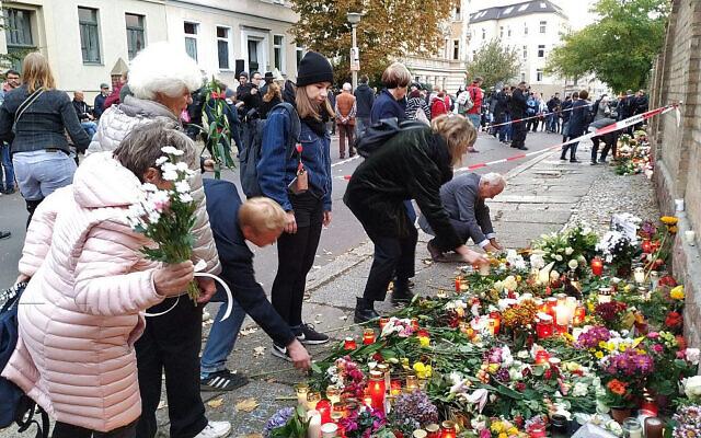Des personnes déposent des fleurs devant la synagogue de Halle, en Allemagne, où un mémorial a été placé pour les victimes de la fusillade de mercredi. Le 11 octobre 2019. (Yaakov Schwartz/ Times of Israel)